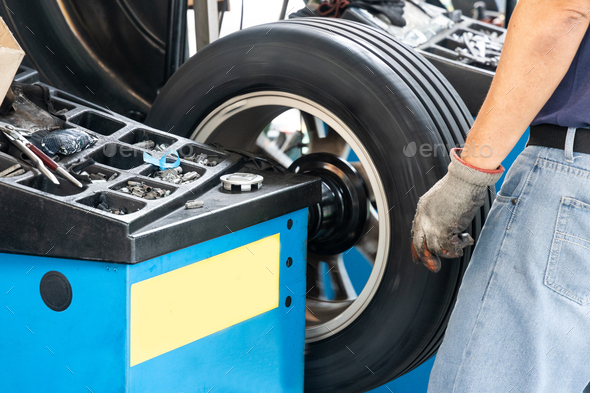 Series of worker balancing tire with wheel balancing machinery - Stock Photo - Images