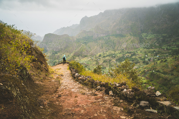 Man enjoying impressive mountainscape. Arid canyon valley extend far below. Santo Antao, Cabo Verde - Stock Photo - Images