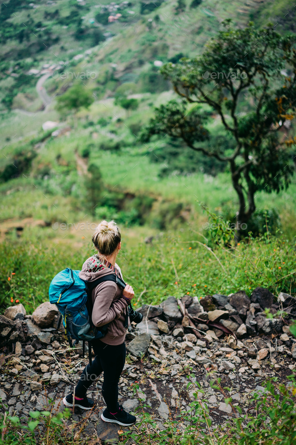 Female hiker with backpack walking down cobbled path to the lush green Paul valley. Santo Antao Cape - Stock Photo - Images