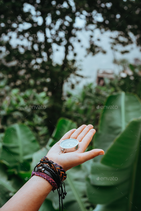 Hand with compass in the lush rainforest jungle - Stock Photo - Images