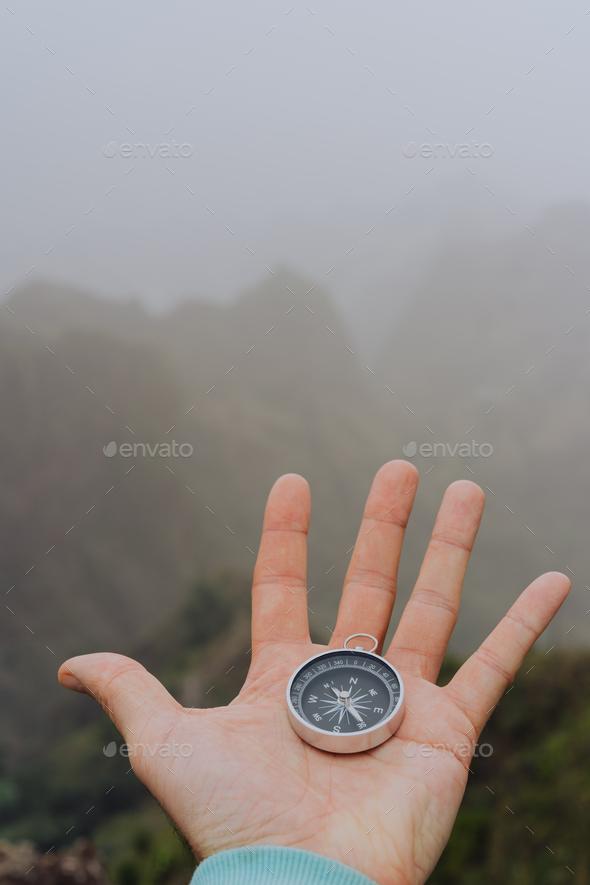 Man palm holding compass. Foggy mountainous landscape - Stock Photo - Images