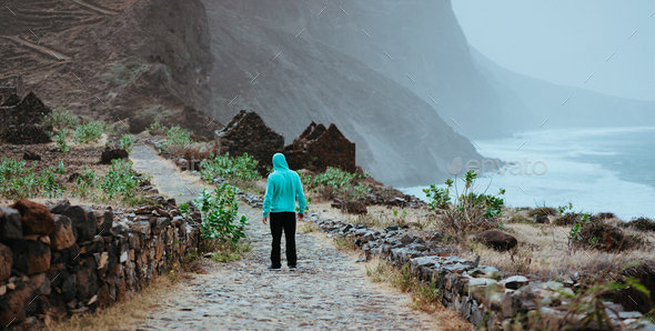 Male hiker admiring beautiful dramatic landscape of rugged coastline on the trekking trail to - Stock Photo - Images