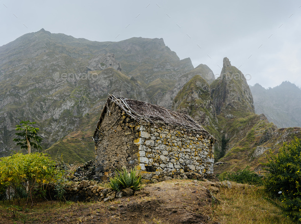 Ruined local storehouse nestled into incredible scenery with steep mountain rocks and vertical peaks - Stock Photo - Images