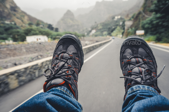 Relaxing feet with trekking footwear hanging from pickup car after long trek way. Santo Antao Island - Stock Photo - Images