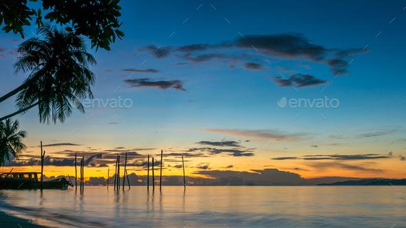 Sunset on Kri Island. Boats under Palmtrees. Raja Ampat, Indonesia, West Papua - Stock Photo - Images