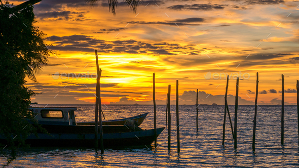 Sunset on Kri Island. Some Boats in Foreground. Raja Ampat, Indonesia, West Papua - Stock Photo - Images