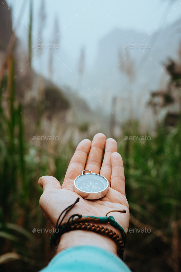 Man arm with compass on the palm stretched out to determine position in mountains on cloudy day - Stock Photo - Images