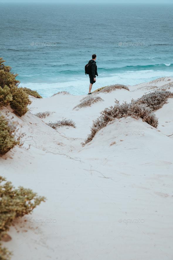 Alone traveler in snow-white dune landscape on the Atlantic coastline - Stock Photo - Images