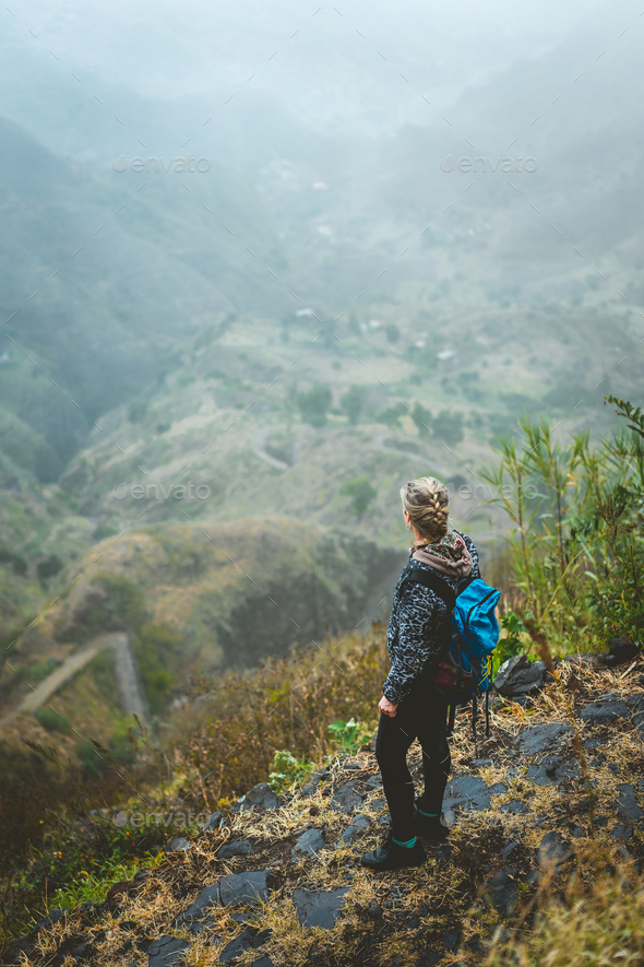 Traveler on cobbled path admiring spectacular lush green valley. Santo Antao island in Cabo Verde - Stock Photo - Images