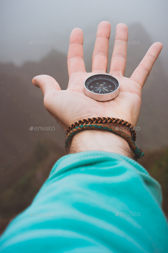 Hand with compass on the rock in front of the monumental mountain range silhouette in the fog - Stock Photo - Images