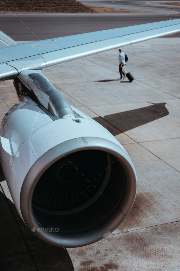 Airplane boarding. Turbine of engine airplane. Traveler with luggege in the background - Stock Photo - Images