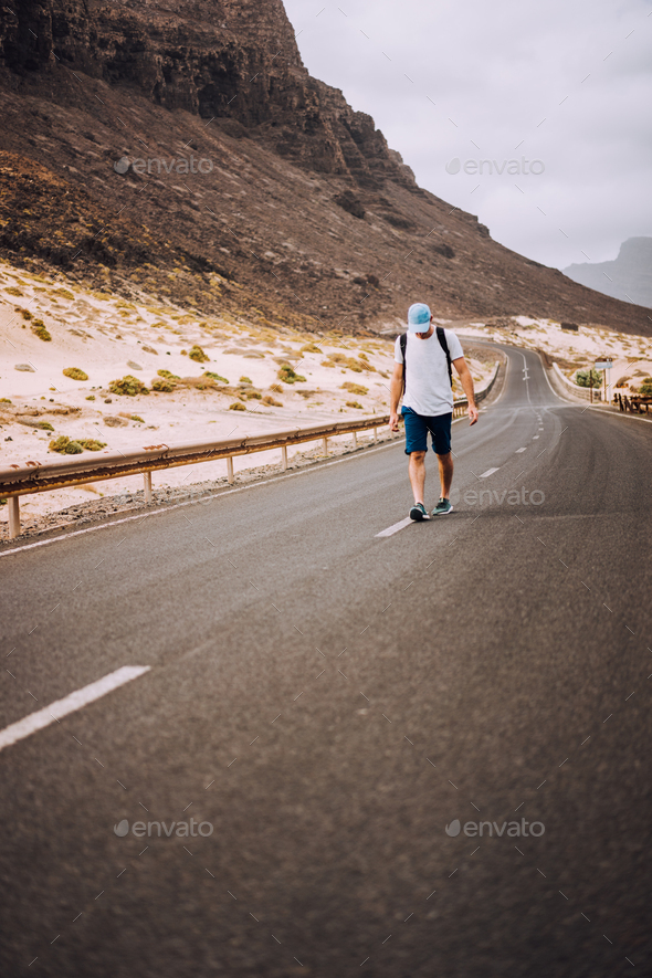 Traveler with backpack standing in the center of an epic winding road. Huge volcanic mountains in - Stock Photo - Images