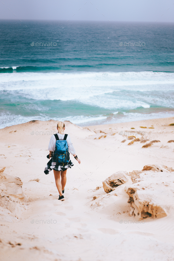 Woman hiker with backpack going down a sand dune towards the lonely beach. Sao Vicente Cape Verde - Stock Photo - Images