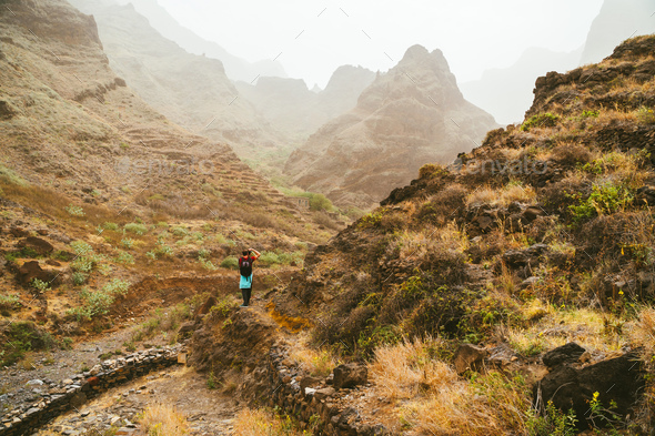 Traveler on great walking destination with stunning views of rugged coast lines and narrow canyons - Stock Photo - Images