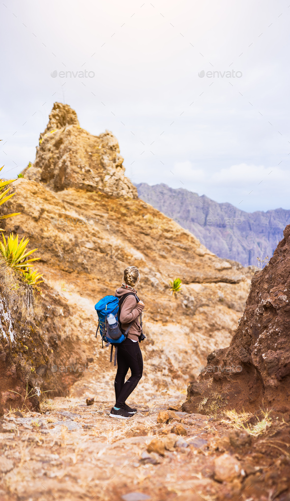 Woman hiker on the stony trekking trail in front of the barren mountain peak on Santo Antao island - Stock Photo - Images