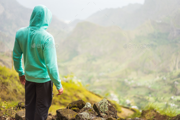Tourist in hoodie in front of rural landscape with mountains, on the way of the Paul Valley. Santo - Stock Photo - Images