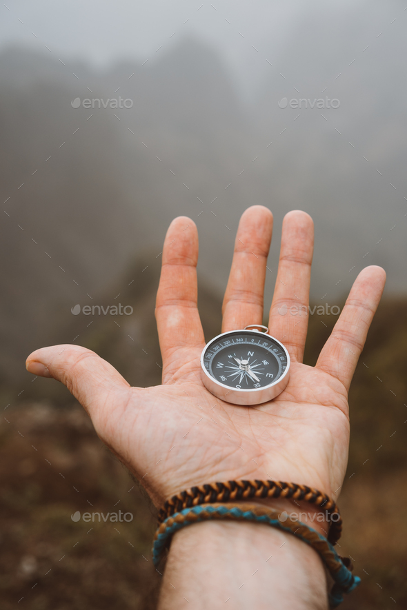 Hand holding a compass. Silhouette of monumental mountain formation in background - Stock Photo - Images