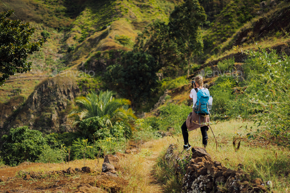 Woman tourist with blue backpack making photo of landscape in Mountains of Santo Antao island, Cabo - Stock Photo - Images