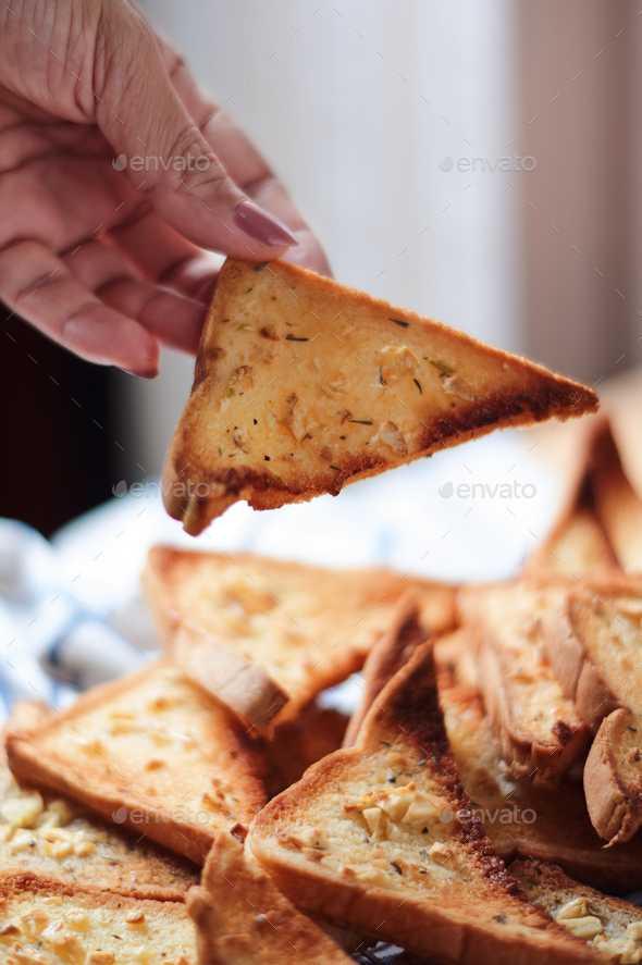 Hand of woman picks a garlic bread - Stock Photo - Images