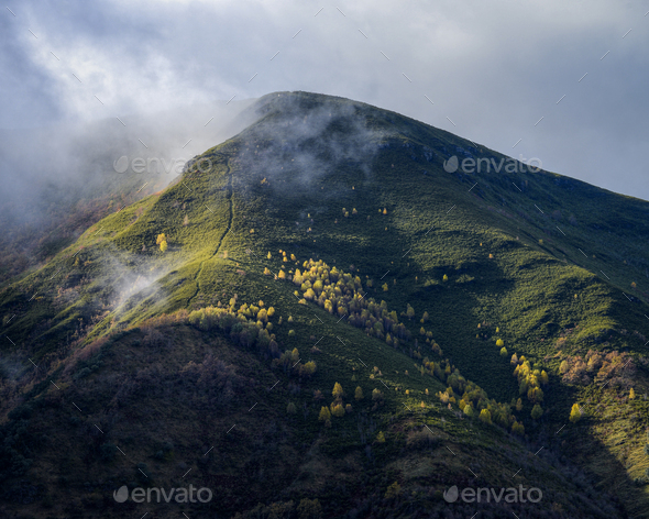 A foot path leads to the top of a foggy mountain - Stock Photo - Images