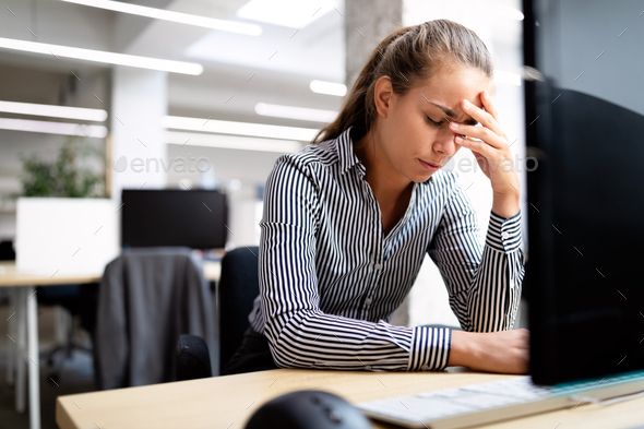 Overworked and frustrated young woman in front of computer in office - Stock Photo - Images