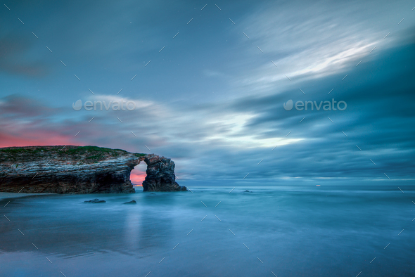 Long exposure of the sunset over the famous stone arch of As Catedrais beach - Stock Photo - Images