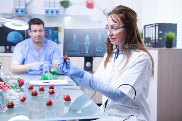 Female scientis with protection gear working in a microbiology research lab - Stock Photo - Images