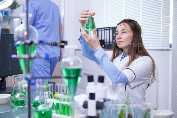 Mature female scientist making scientific test in her research lab - Stock Photo - Images