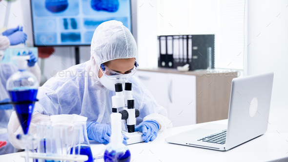 Caucasian chemist is watching a reaction under the microscope - Stock Photo - Images