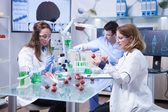 Caucasian woman with protection glasses doing scientific test on strawberries - Stock Photo - Images