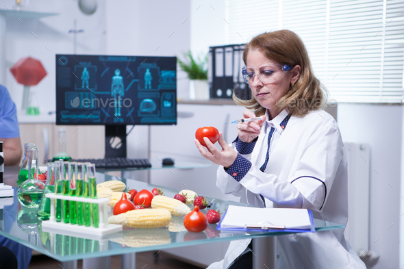 Biologist in white coat in a research lab injecting liquid in a tomato - Stock Photo - Images