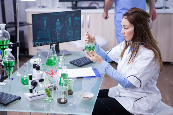 Mature scientist working with a green solution in a research lab - Stock Photo - Images