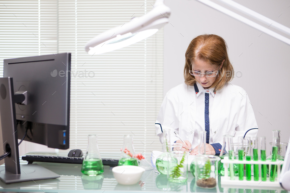 Focused middle age woman taking notes after scientific test in a production laboratory - Stock Photo - Images
