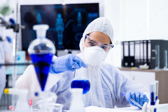 Researcher mixing a blue liquid in a tube and looking at it - Stock Photo - Images