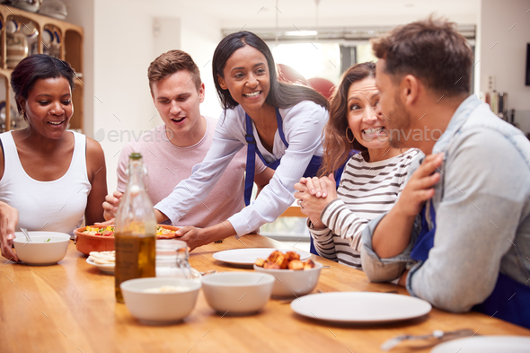 Group Of Friends Sitting Around Table Eating Meal At Home Together - Stock Photo - Images