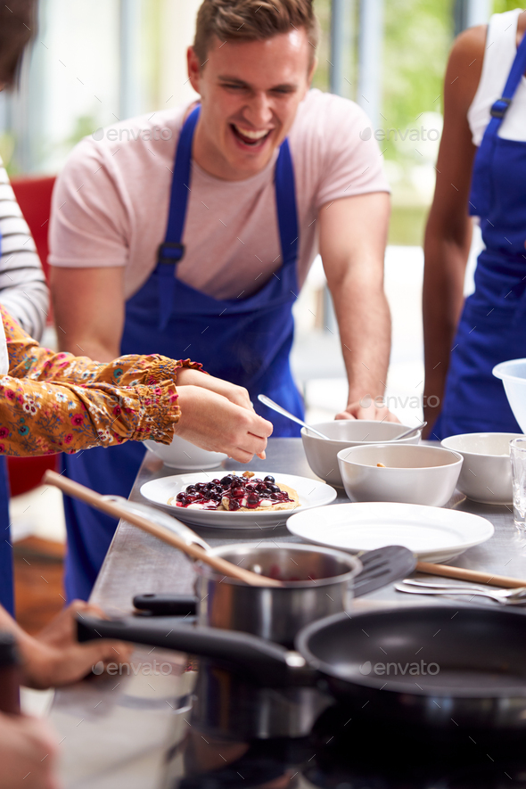 Students Watching Female Teacher Decorating Pancake In Cookery Class - Stock Photo - Images