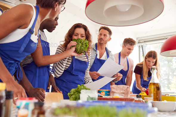Male And Female Adult Students Looking At Recipe And Smelling Ingredients In Cookery Class - Stock Photo - Images