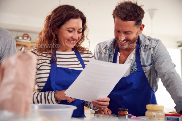 Mature Male And Female Adult Students Looking At Recipe In Cookery Class In Kitchen - Stock Photo - Images