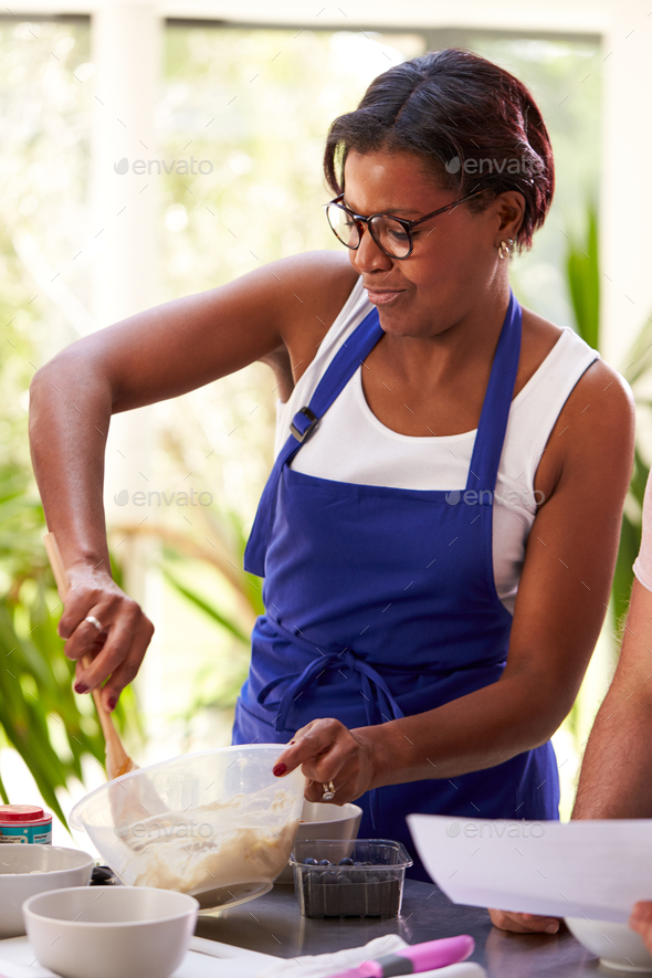 Female Student Mixing Ingredients For Recipe In Cookery Class In Kitchen - Stock Photo - Images
