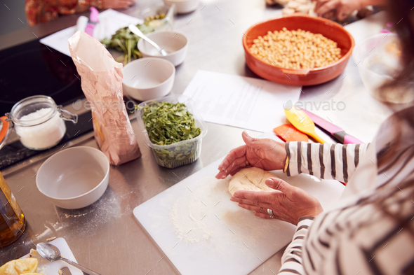 Close Up Of Female Teacher Demonstrating How To Use Dough To Make Flatbread In Cookery Class - Stock Photo - Images