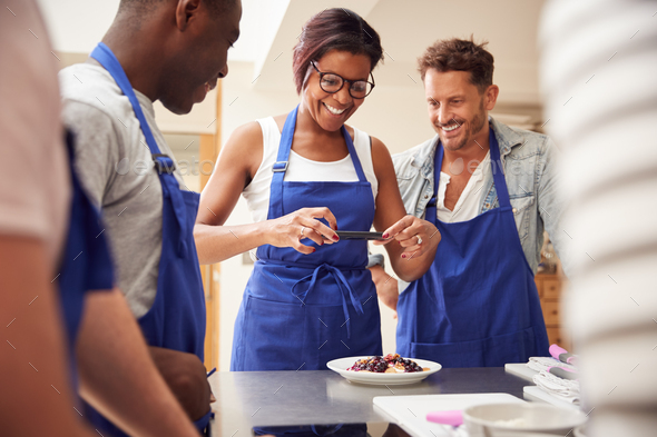 Woman Taking Photo Of Pancake Dish For Social Media In Cookery Class - Stock Photo - Images