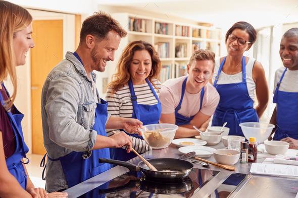 Male Teacher Making Pancake On Cooker In Cookery Class As Adult Students Look On - Stock Photo - Images