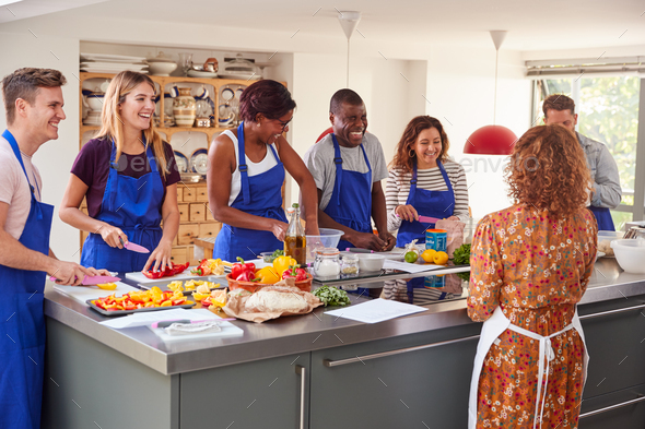 Male And Female Adult Students With Teacher Preparing Ingredients For Dish In Kitchen Cookery Class - Stock Photo - Images