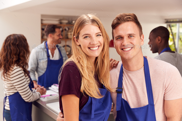 Portrait Of Smiling Couple Wearing Aprons Taking Part In Cookery Class In Kitchen - Stock Photo - Images