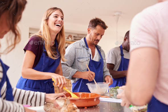 Male And Female Adult Students Preparing Ingredients For Dish In Kitchen Cookery Class - Stock Photo - Images
