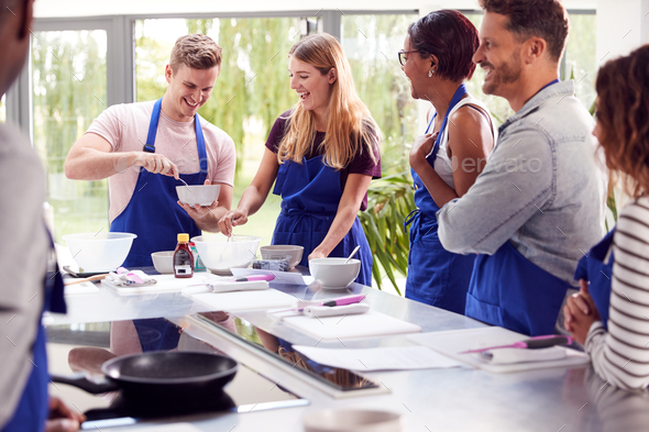 Male And Female Adult Students Measuring Ingredients In Cookery Class In Kitchen - Stock Photo - Images