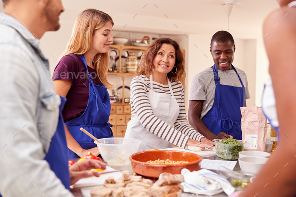 Female Teacher Demonstrating How To Use Dough To Make Flatbread In Cookery Class - Stock Photo - Images