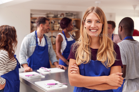 Portrait Of Smiling Woman Wearing Apron Taking Part In Cookery Class In Kitchen - Stock Photo - Images