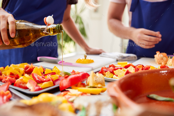 Close Up Of Olive Oil Being Poured On Tray Of Peppers In Kitchen Cookery Class - Stock Photo - Images