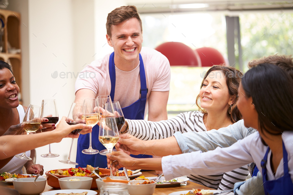 Group Of Men And Women Making Toast As They Enjoy Eating Meal Prepared In Kitchen Cookery Class - Stock Photo - Images